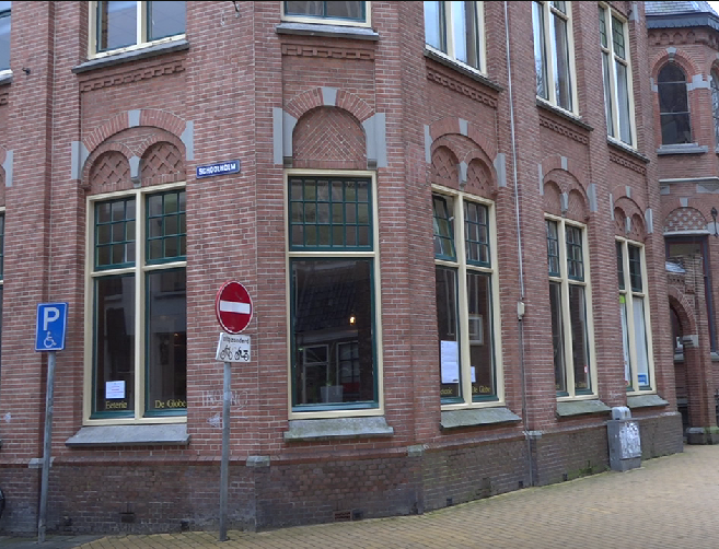 Image of the outside of Eeterie De Globe in Groningen, The Netherlands. Red Bricks, large green windows and a delicious smell from the inside.