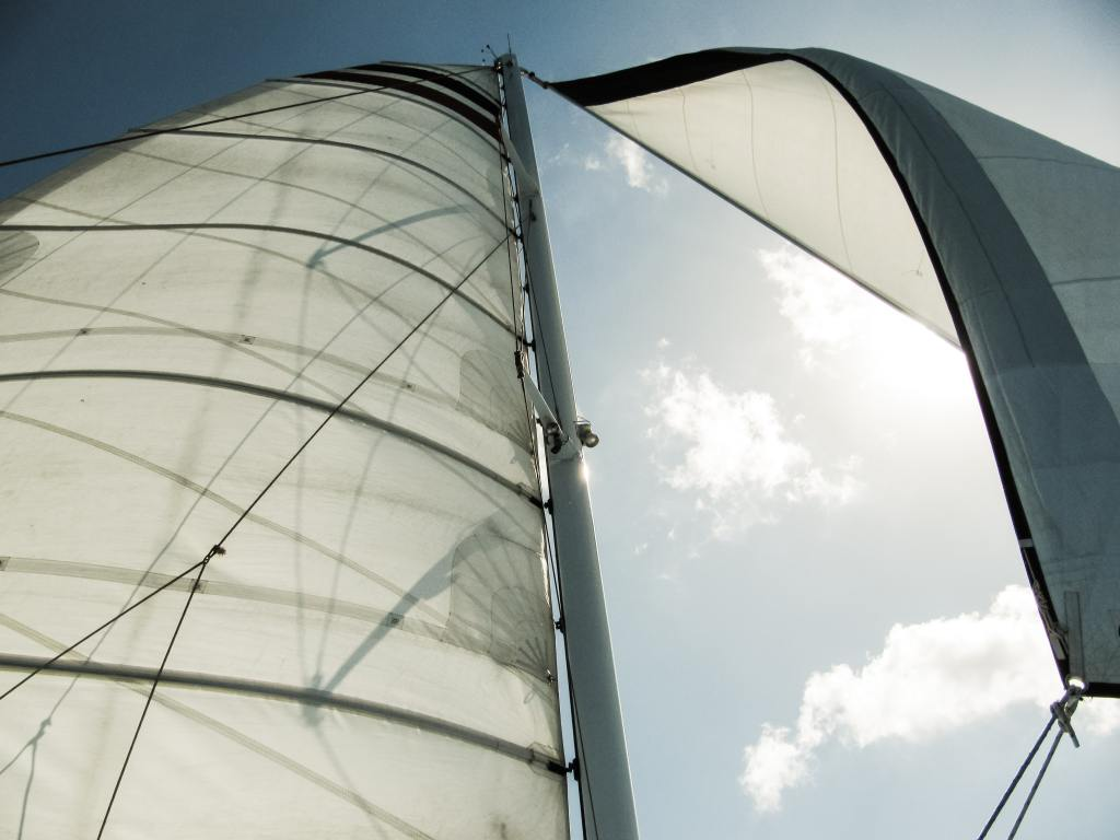 Image of a sail from a large sailboat in under clear blue skies